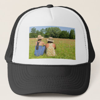 Two friends sitting together in meadow.JPG Trucker Hat