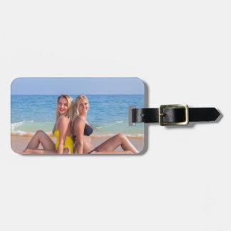 Two girls sit on beach near blue sea.JPG Luggage Tag