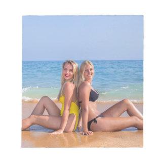 Two girls sit on beach near blue sea.JPG Notepad