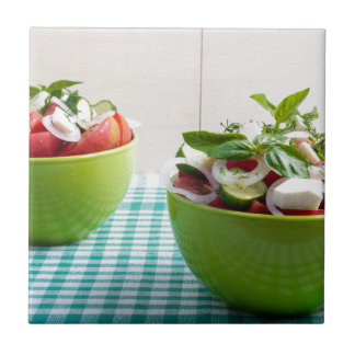 Two green bowl with vegetable vegetarian salad small square tile
