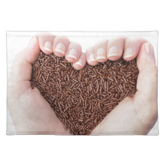 Two hands holding chocolate sprinkles placemat