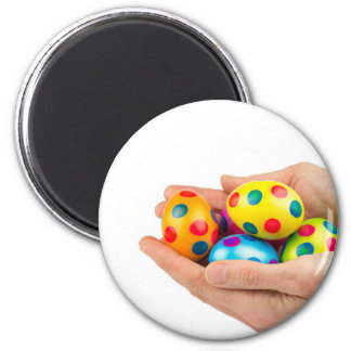 Two hands holding  painted easter eggs on white magnet