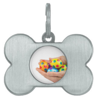 Two hands holding  painted easter eggs on white pet ID tag