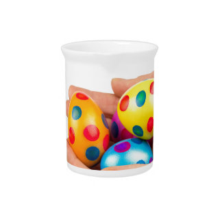Two hands holding  painted easter eggs on white pitcher