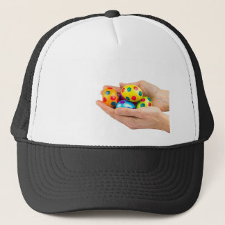Two hands holding  painted easter eggs on white trucker hat