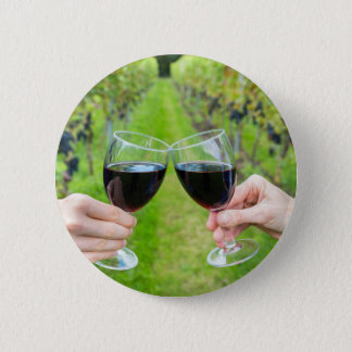 Two hands toasting with wine glasses in vineyard 6 cm round badge