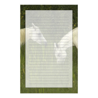 Two horses eating grass stationery