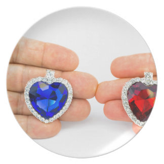 Two jewelry hearts on hand of man and woman dinner plates