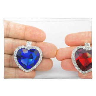Two jewelry hearts on hand of man and woman placemat