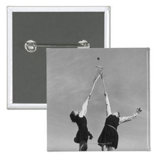 Two lacrosse players jump for the ball. 15 cm square badge