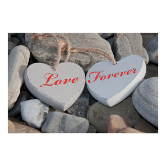 two love hearts on a rocky beach as one poster