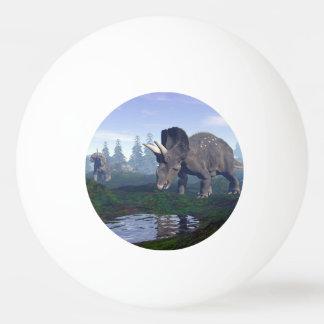 Two nedoceratops/diceratops dinosaurs walking ping pong ball