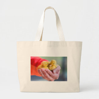 Two newborn yellow ducklings sitting on hand large tote bag