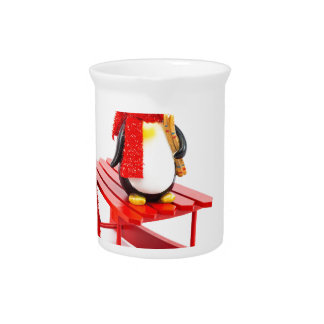 Two penguins with sleigh and christmas tree pitcher