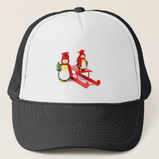 Two penguins with sleigh and christmas tree trucker hat