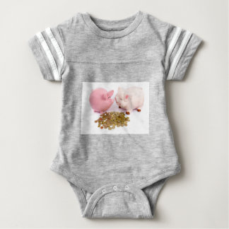 Two piggy banks with euro coins on white baby bodysuit