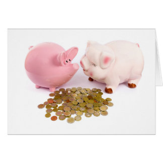 Two piggy banks with euro coins on white card