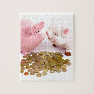 Two piggy banks with euro coins on white jigsaw puzzle
