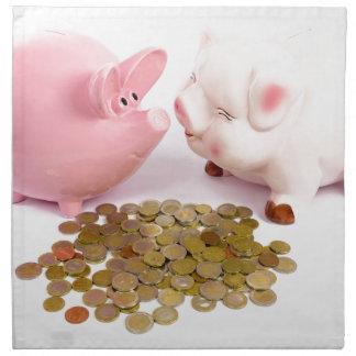 Two piggy banks with euro coins on white napkin