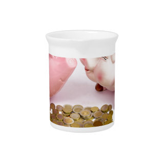 Two piggy banks with euro coins on white pitcher