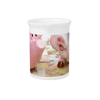 Two pink piggy banks on spread euro notes beverage pitcher