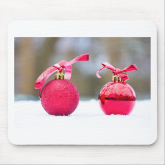 Two red christmas balls outside in snow mouse pad