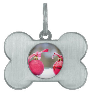 Two red christmas balls outside in snow pet name tag