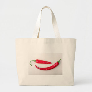 Two red hot chili peppers closeup large tote bag