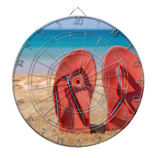 Two red slippers upright in sand of beach.JPG Dartboard