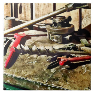 Two Red Wrenches on Plumber's Workbench Tile