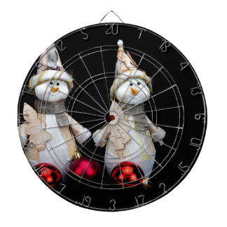 Two snowmen figurines with red baubles on black dartboard