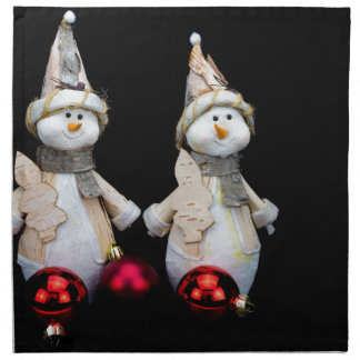 Two snowmen figurines with red baubles on black napkin