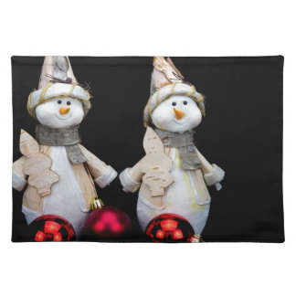 Two snowmen figurines with red baubles on black placemat