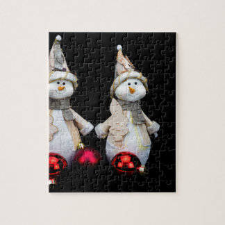 Two snowmen figurines with red baubles on black puzzle