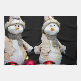 Two snowmen figurines with red baubles on black tea towel