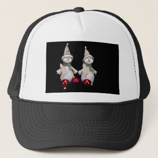 Two snowmen figurines with red baubles on black trucker hat