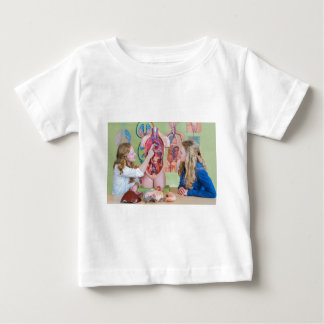 Two students learning model human body in biology. baby T-Shirt