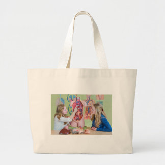 Two students learning model human body in biology. large tote bag