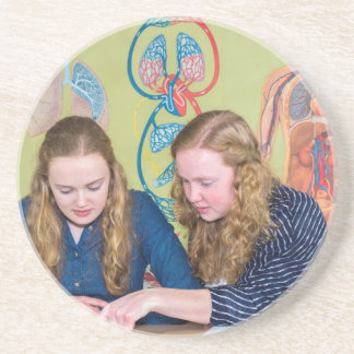 Two students learning with books in biology lesson coaster