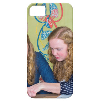 Two students learning with books in biology lesson iPhone 5 case