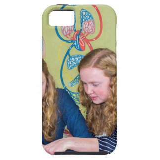 Two students learning with books in biology lesson iPhone 5 cases