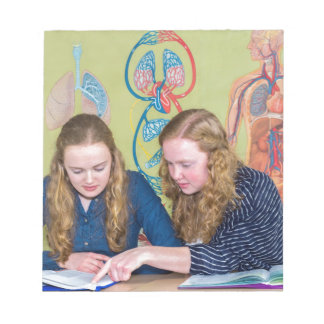 Two students learning with books in biology lesson notepad