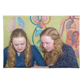 Two students learning with books in biology lesson place mats