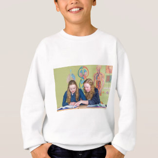 Two students learning with books in biology lesson sweatshirt