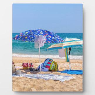 Two sun umbrellas and beach supplies at sea.JPG Plaque