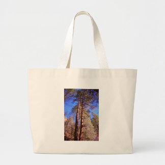 two trees in the woods tote bags