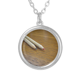 Two used colored pencils on wooden table silver plated necklace
