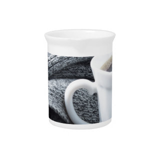 Two white cups of coffee wrapped in scarf pitcher