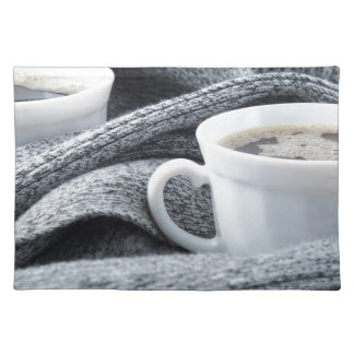 Two white cups of coffee wrapped in scarf placemats