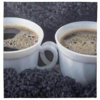 Two white cups with black coffee and foam napkin